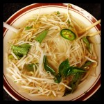 bowl of vietnamese pho noodles with basil leaves, bean sprouts, and jalapenos