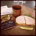 panera bread sandwich and pickle with side of potato chips