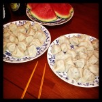 plates of homemade dumplings with watermelon in background