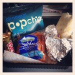snacks on plane for united flight from us to uk including twix bar, popchips bag, bag of baby carrots, and burrito