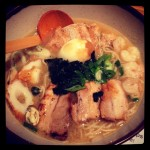 bowl of wagamama ramen dish with pork, shrimp, wakame seaweed, and fish cakes