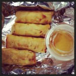 four vietnamese spring rolls with fish sauce on aluminum foil