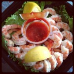 platter of shrimp cocktail with lemons and cocktail sauce