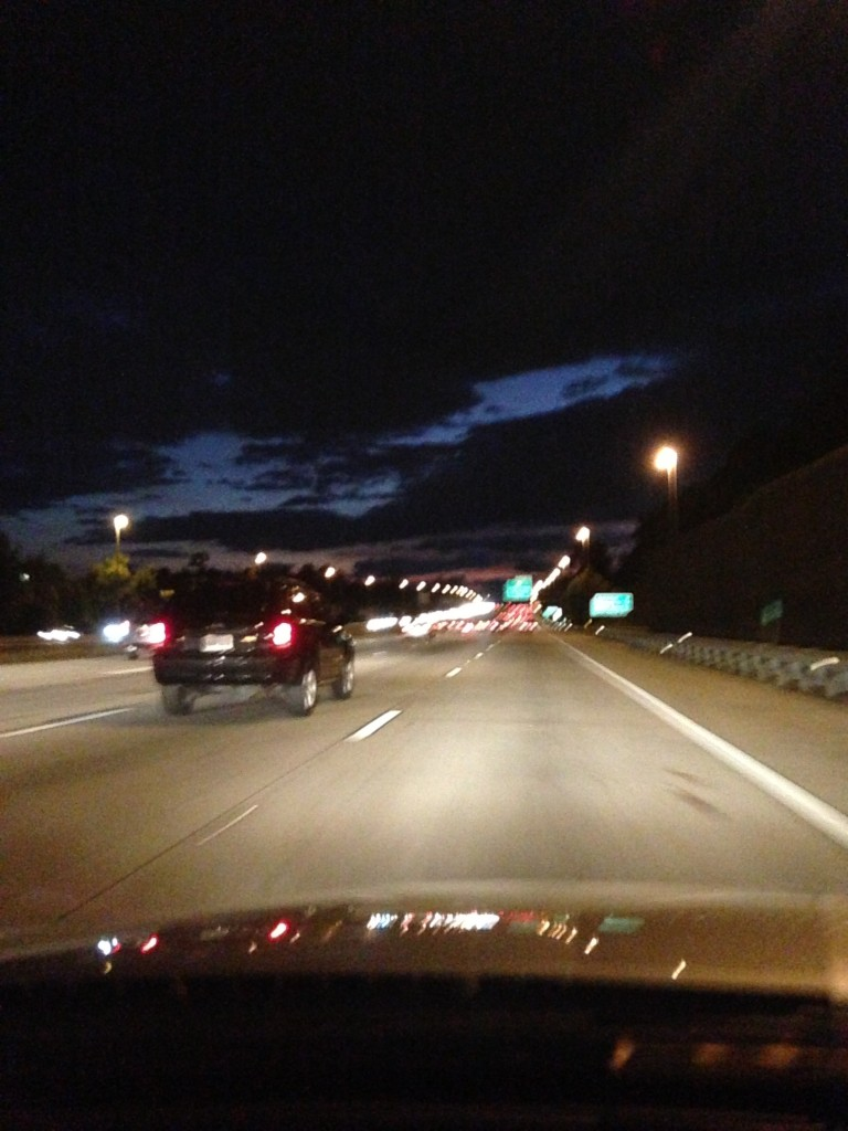 driving on freeway at night with lights dotting road and clouds darkening sky