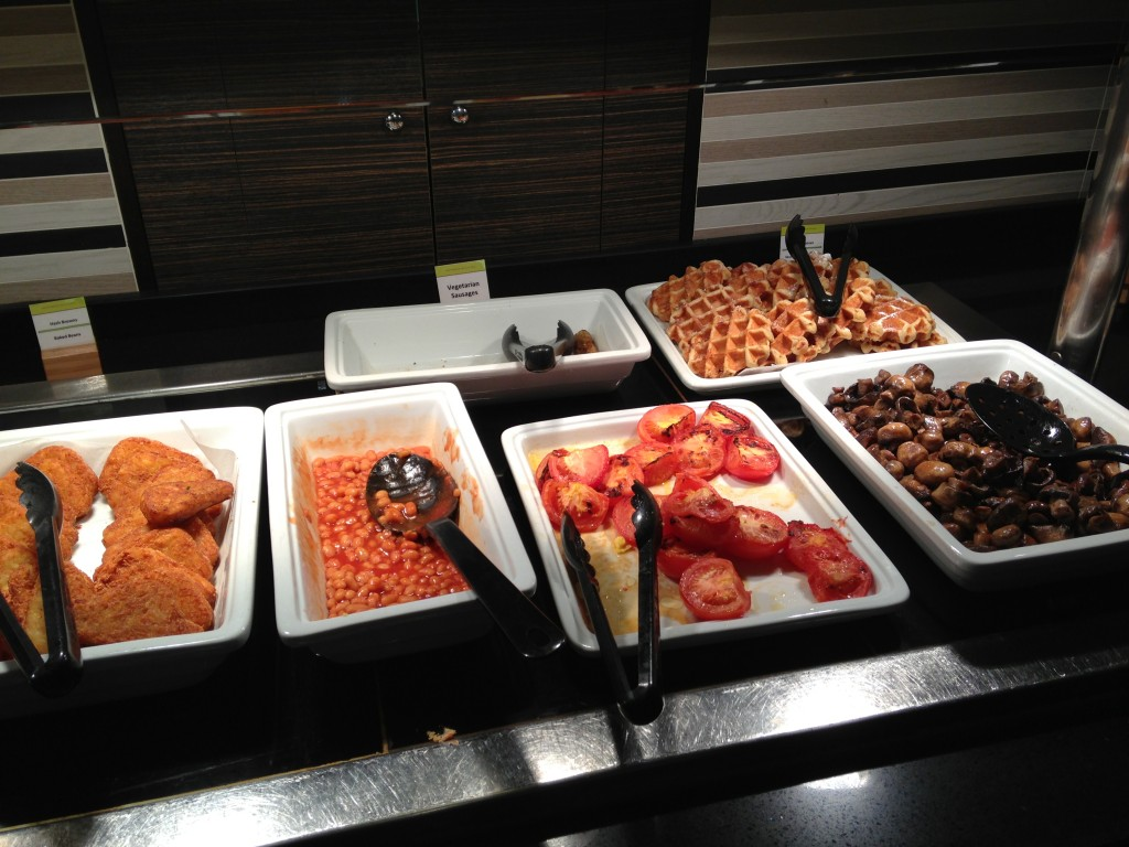 english breakfast buffet with hash browns, baked beans, roasted tomatoes, mushrooms, and waffles