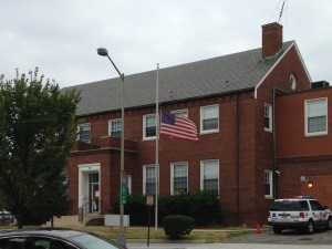 american flag billowing at half mast in front of police station