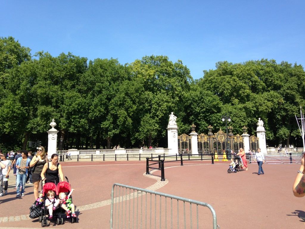 view of gates to green park and tourists walking around outside buckingham palace
