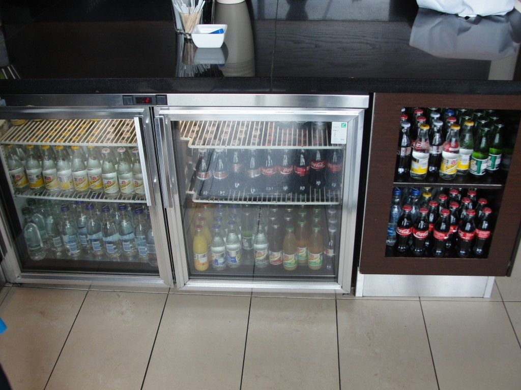 fridge and shelves with small glass bottles of sodas and drinks