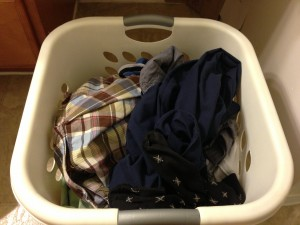 white sqaure laundry basket with clothes piled inside