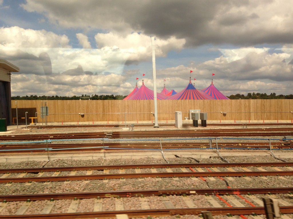 pink and blue striped circus tents beyond railroad tracks