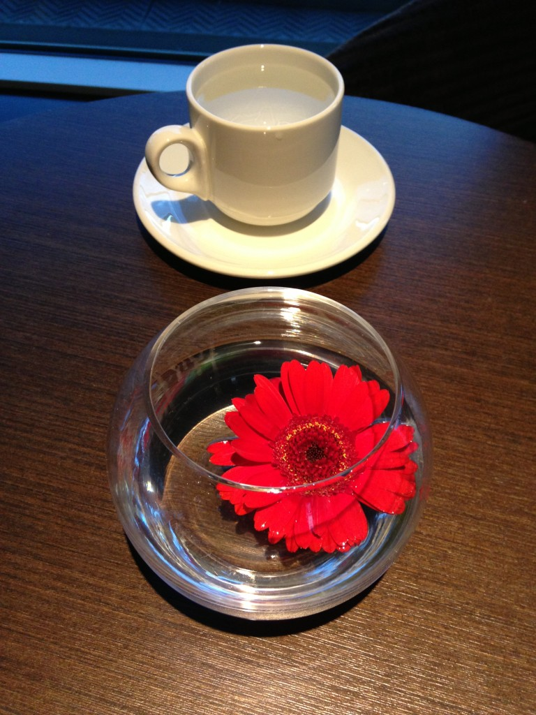 red flower floating in water as centerpiece with mug of water on table