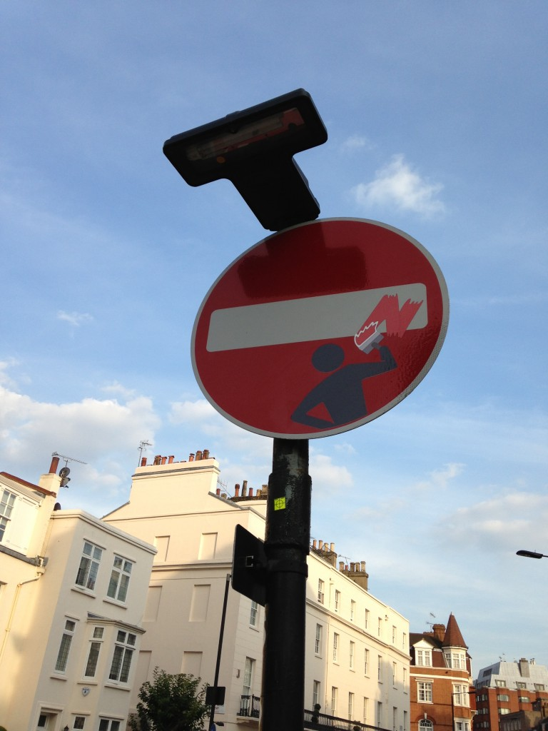 red and white street sign with sticker grafitti