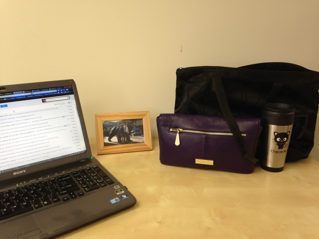 light wood desk with laptop, wooden framed picture, purple purse, black bag, and chococat mug