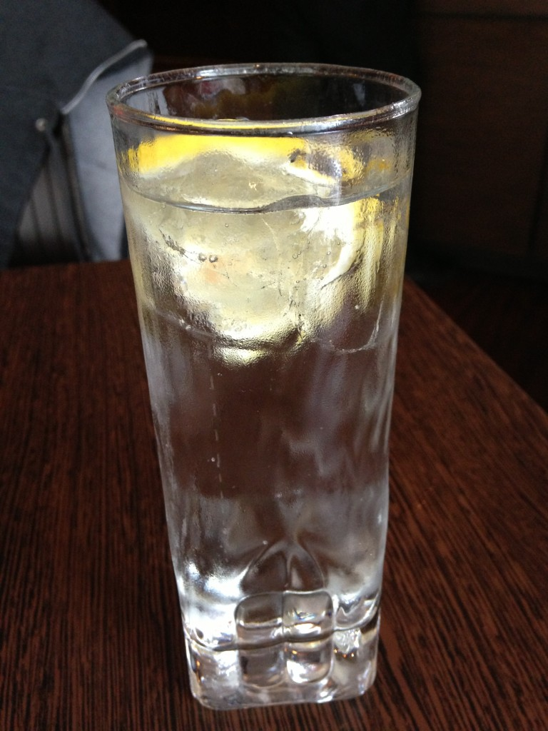 glass of clear sparkling lemonade drink with lemon slice inside