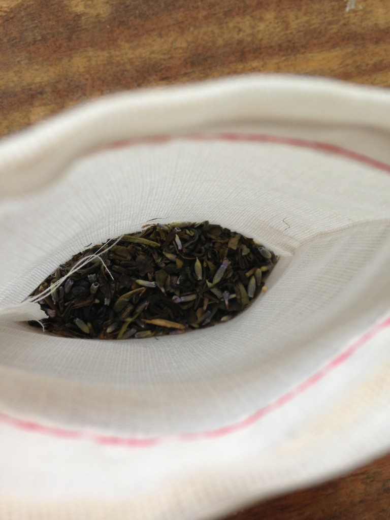 pile of green tea mixed with fresh lavender for bath soak in muslin bag