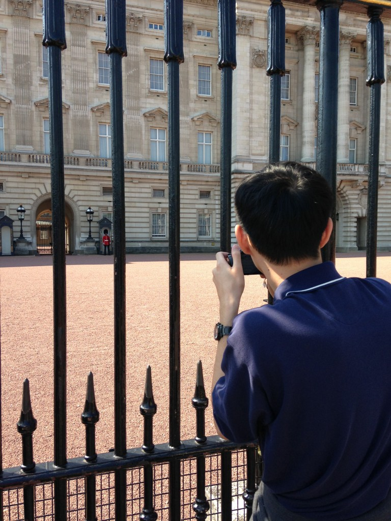 tourist taking picture of buckingham palace guard