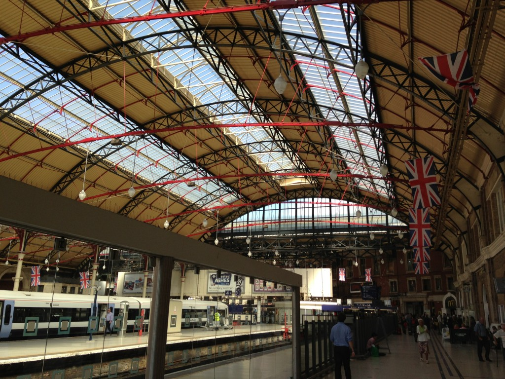 interior of victoria station in london with skylights and british flags
