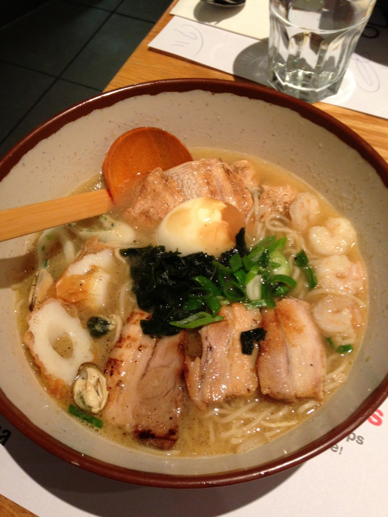 bowl of wagamama ramen dish with pork, shrimp, wakame seaweed, fish cakes, and tea egg