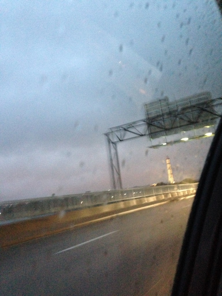 view of washington monument with lights lighting it up seen from car driving away in rain