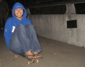 smiling girl in hoodie sitting on skateboard going down hill