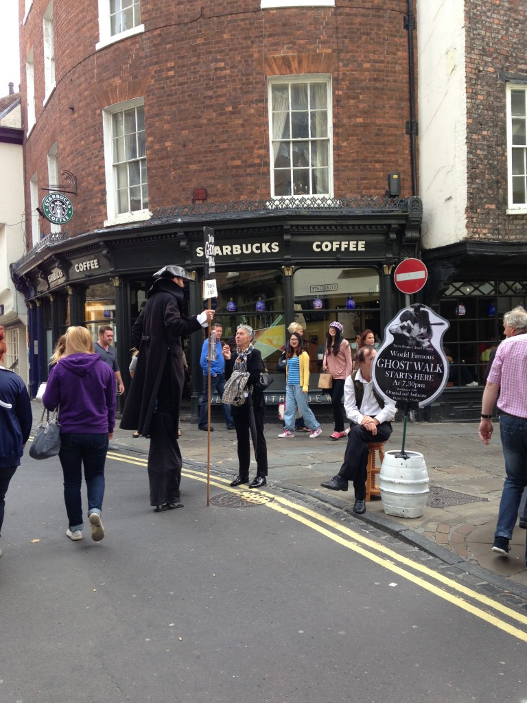 guy on stilts and man with ghost walk sign promoting york ghost walks