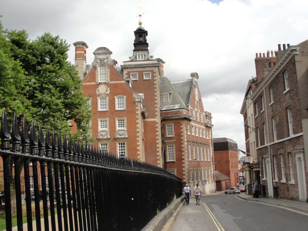 pathway in york with red brick buildings and black metal fence