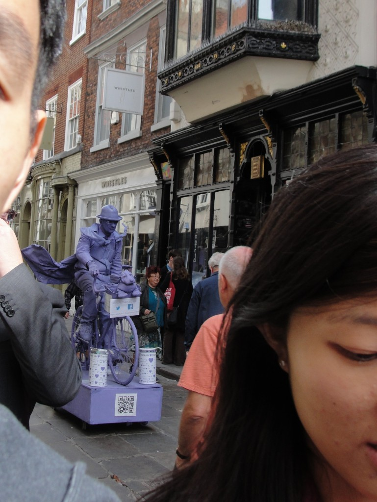 purple windblown street performer frozen on bike in middle of road in york