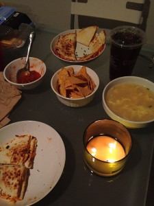 quesadillas, tortilla chips, salsa, egg drop soup, iced tea, and a candle on dinner table