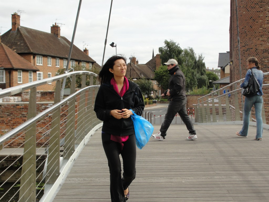 walking on bridge holding plastic bag with wind blowing hair around