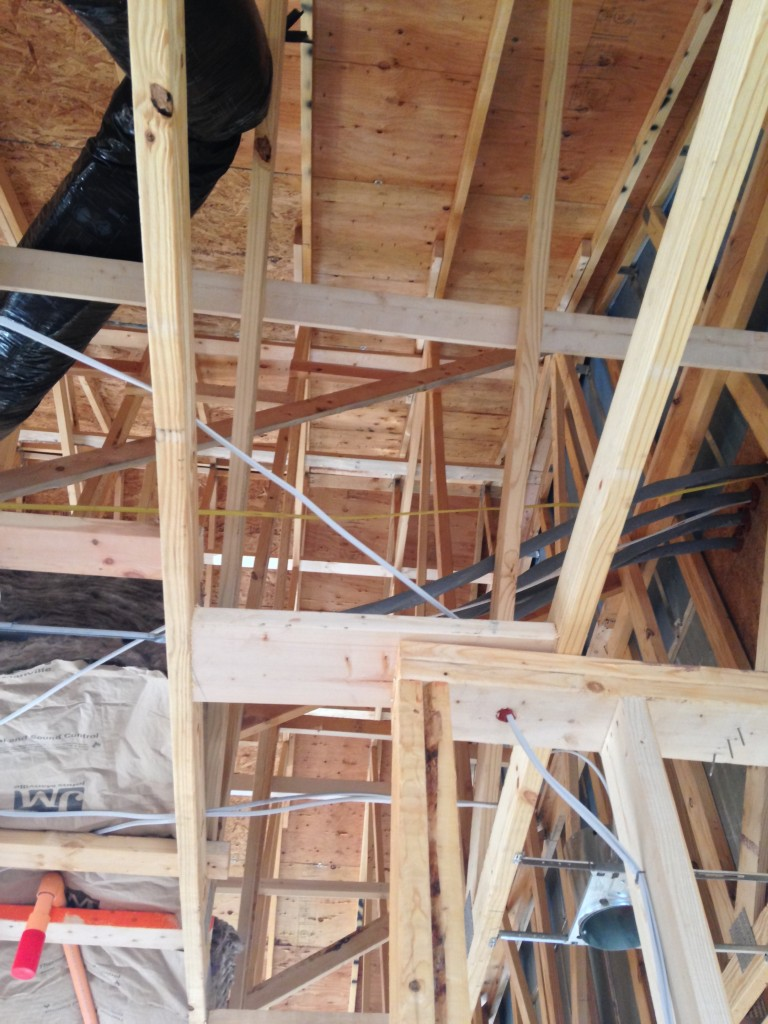 view upwards of wood beams supporting interior of condo frame mid-construction