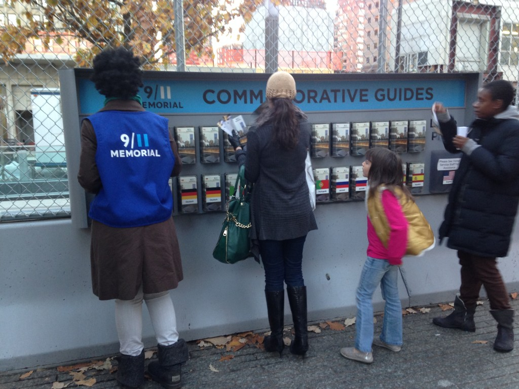 9/11 memorial commemorative guides with people browsing and worker replacing brochures