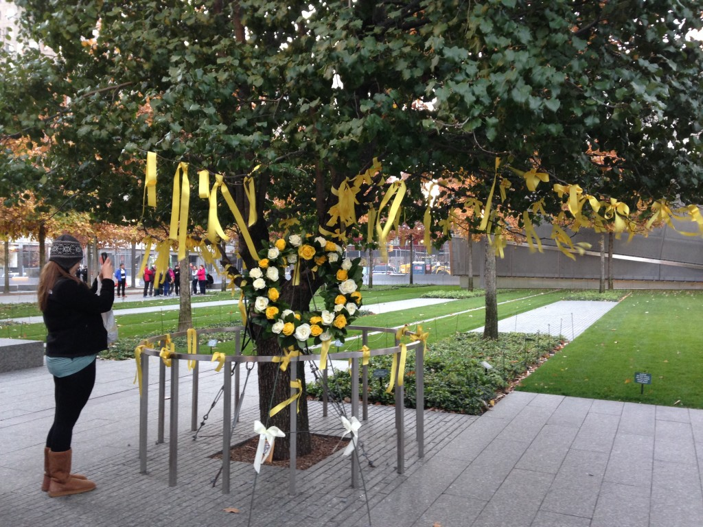 9/11 memorial tree with yellow ribbons and wreath with yellow and white flowers