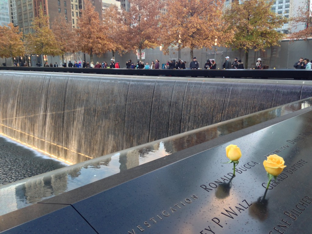 9/11 memorial falling water with yellow roses on names and people lined up looking out