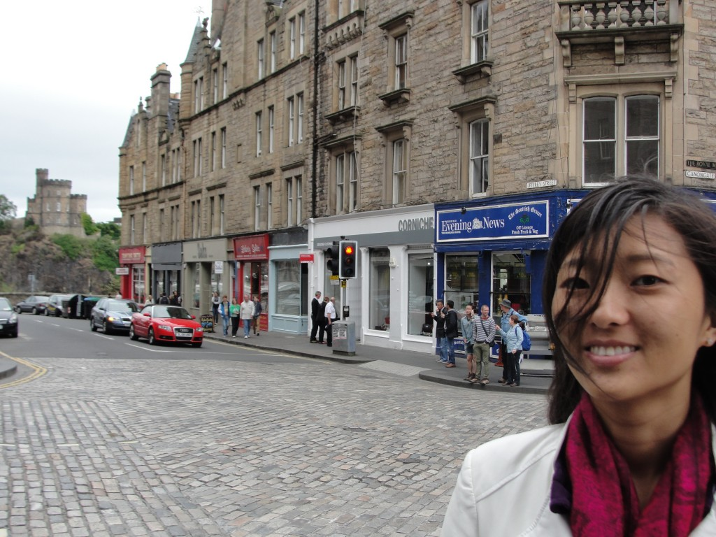 girl standing with hair blown in face on streets of edinburgh