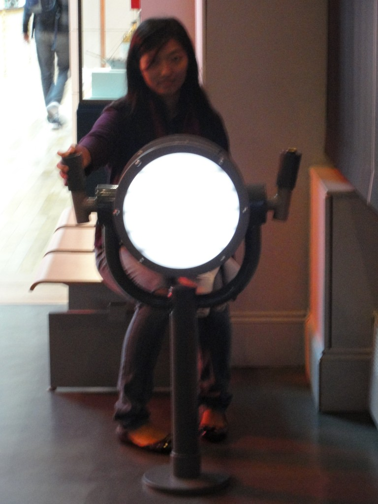 girl sitting in museum using giant light to signal morse code