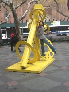 posing on bright yellow street art sculpture in park in nyc