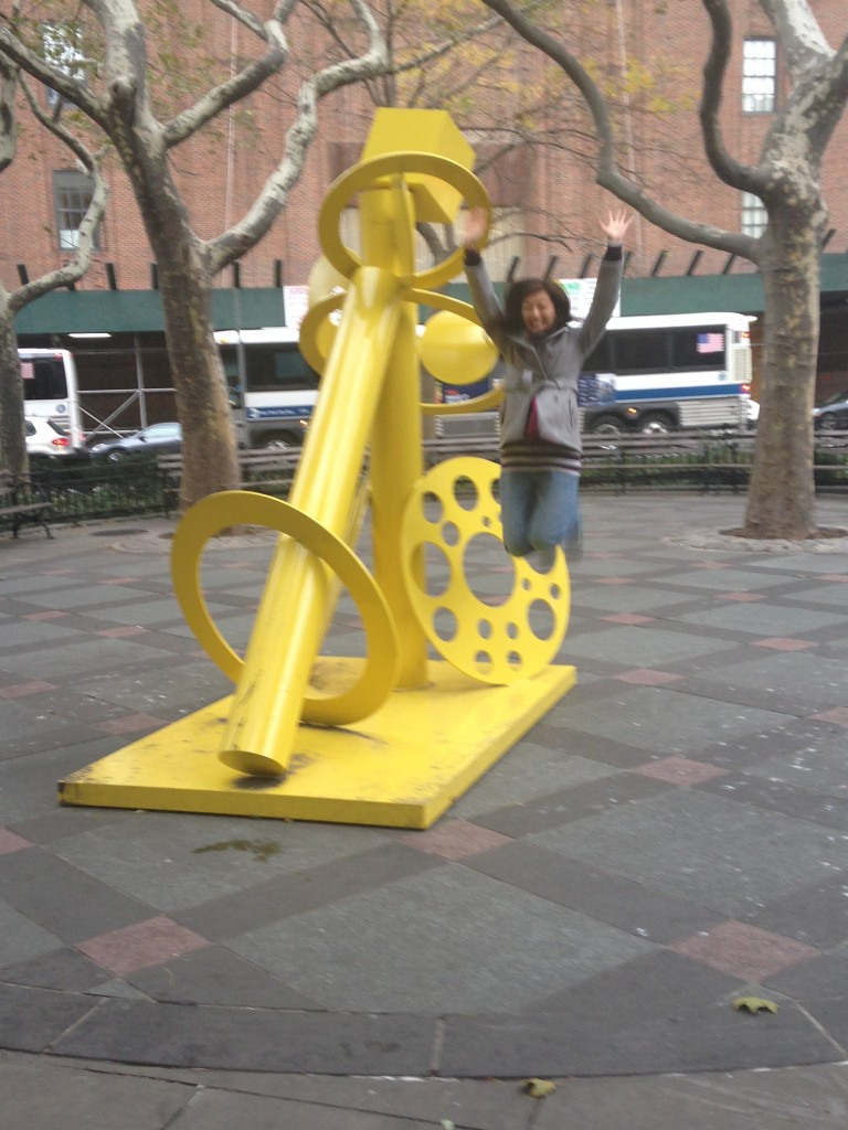jumping off of and next to giant yellow sculpture in small park in new york city