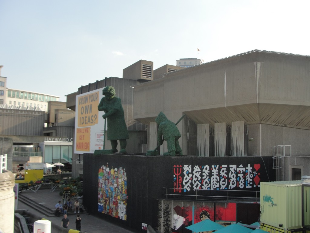 large statues and mural by waterloo bridge in london