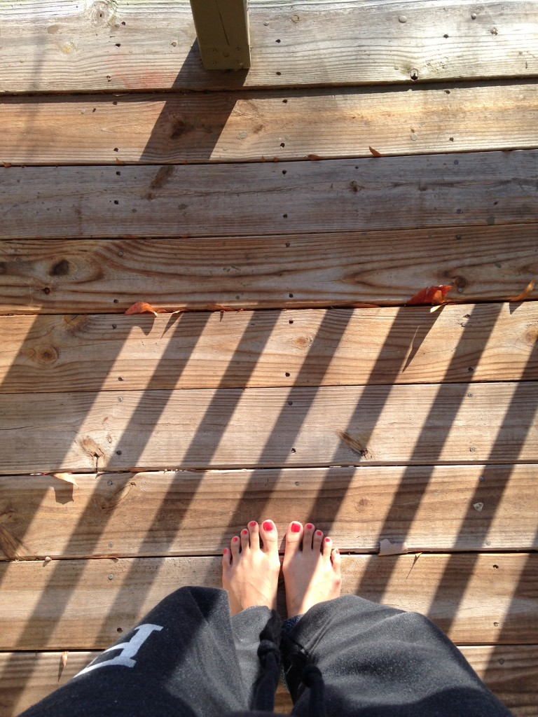 barefoot on porch in sunlight with shadows of railing