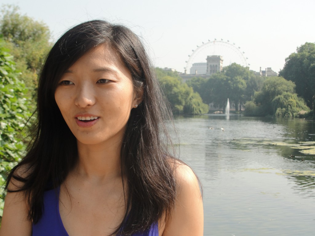 girl mid-talking in front of st. james's park lake with view of london eye in background
