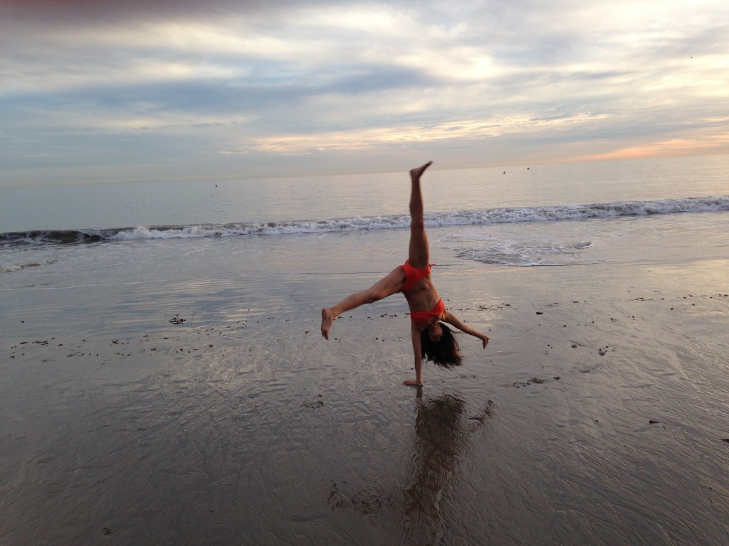 girl in orange bikini doing cartwheel at beach paused on one hand