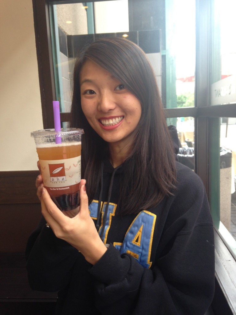 girl smiling holding up cha for tea peach iced tea drink with boba