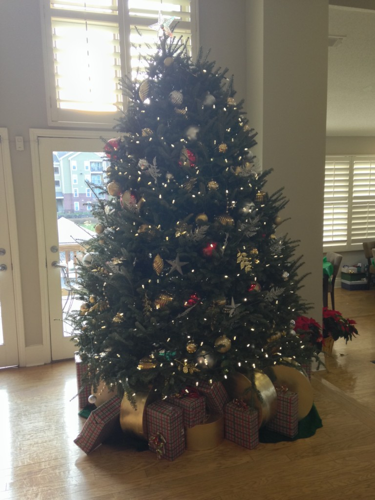 christmas tree with presents underneath set up at rental office of apartment complex