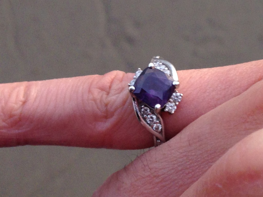 engagement ring with purple sapphire center stone worn on guy's pinky finger