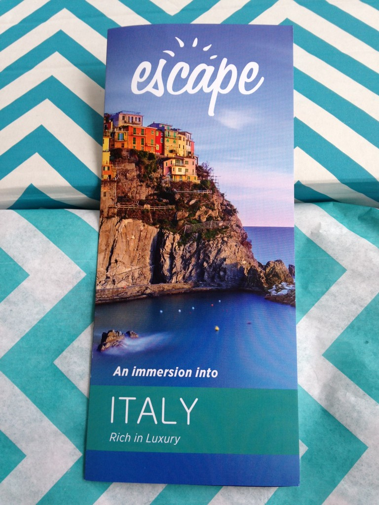escape monthly december italy box info card against blue and white chevron background