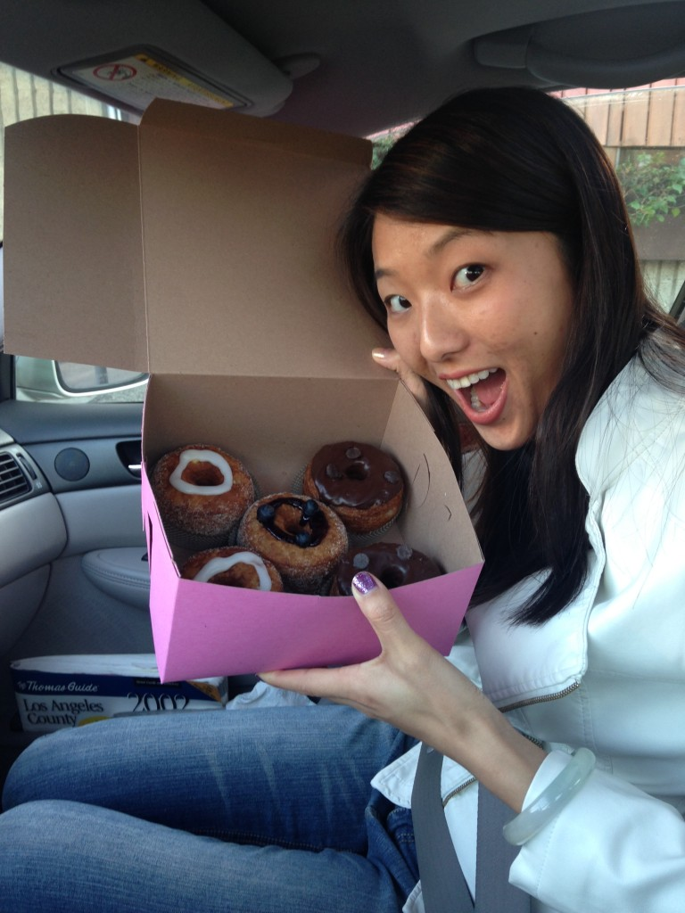 excited girl holding up box of cronuts in car