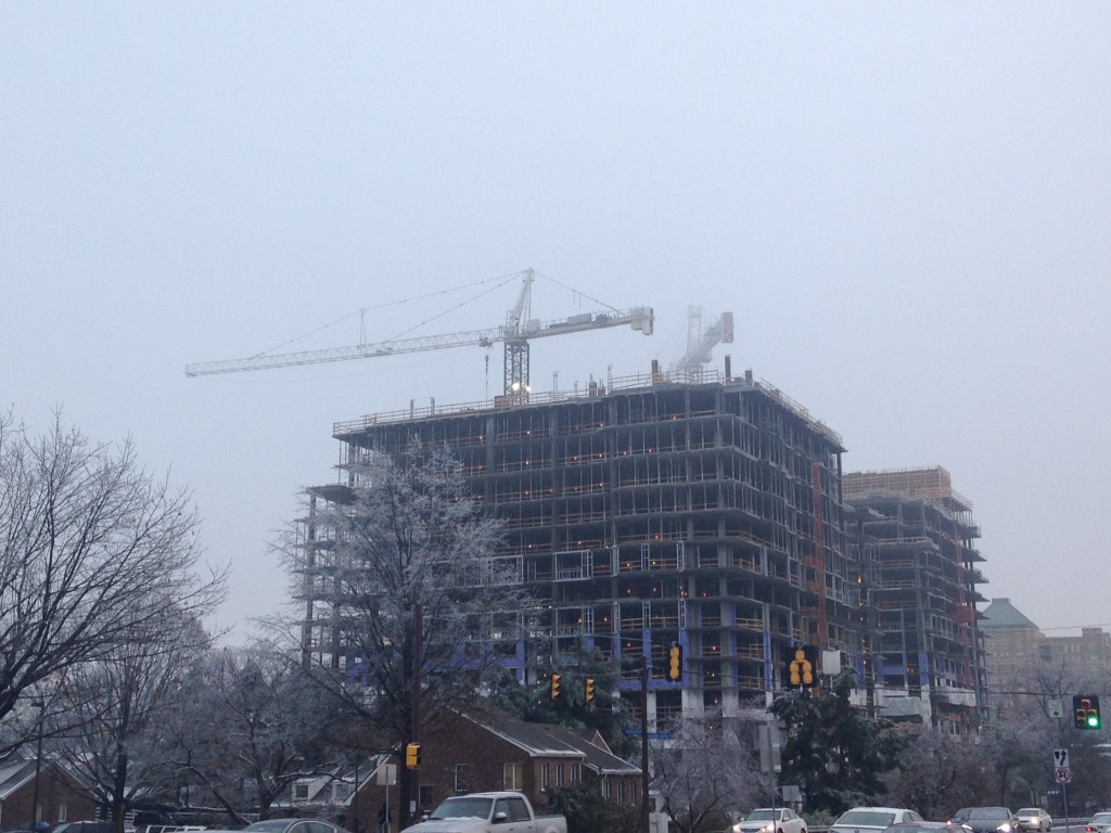thickening fog obscuring cranes atop new construction building