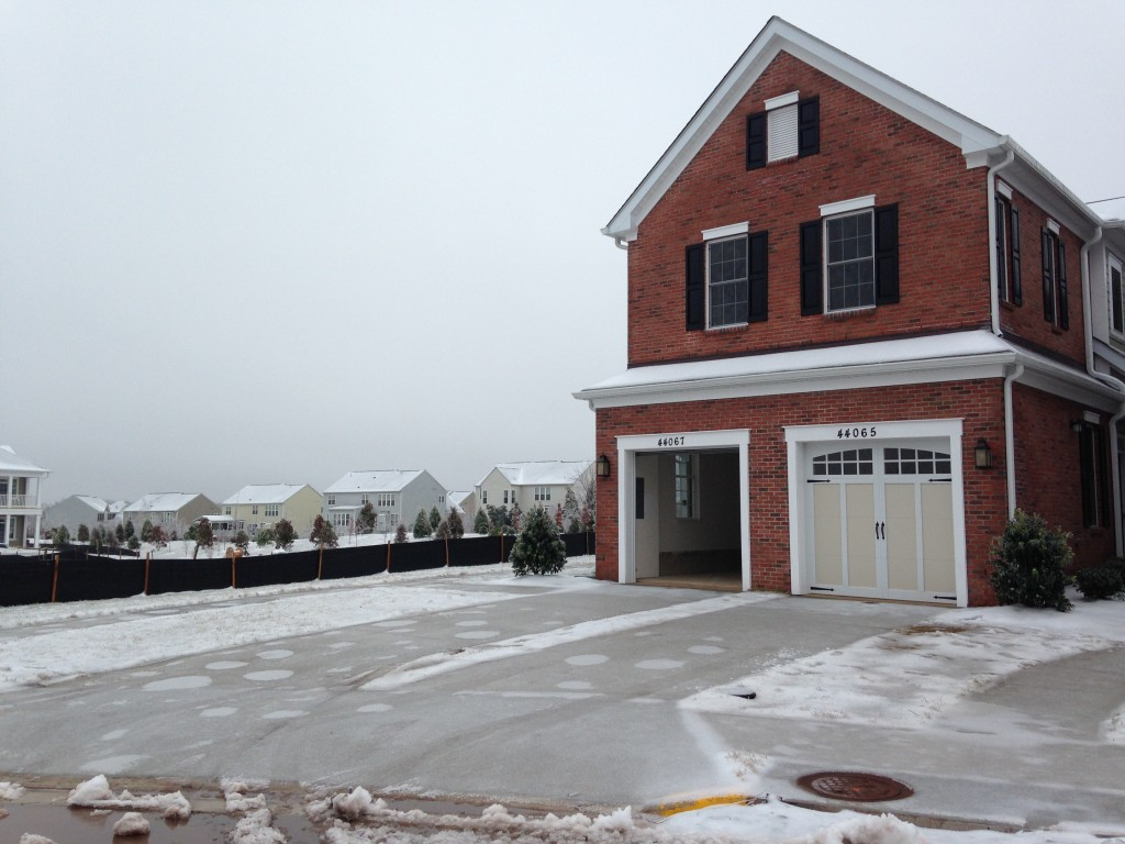 front of new condo with frozen driveway, one garage door open and one closed, and brick facade