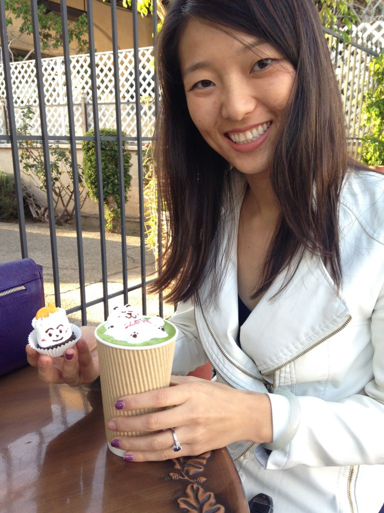 girl holding drink with latte art and decorated marshmallow