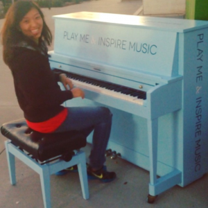 girl at outdoor piano smiling with gleeful expression of joy